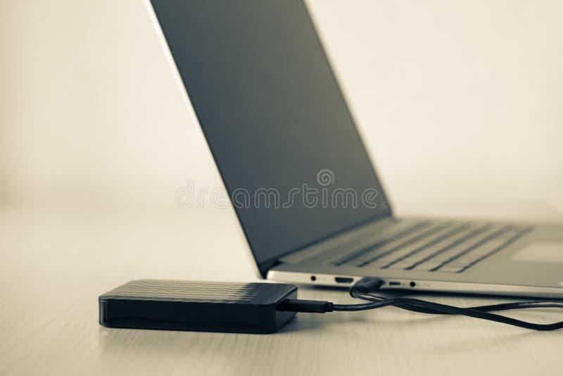 Disco duro externo conectado con mini cable USB a portátil, conexión de fondo de color verde fotos de archivo