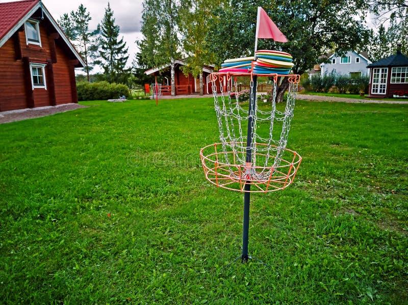 Disco em uma cesta do golfe do disco imagem de stock