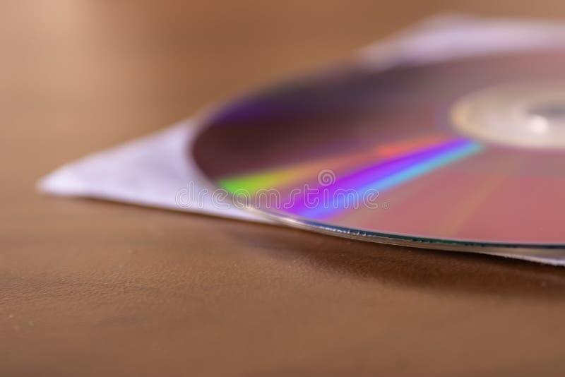 Disco en la tabla de madera, disco compacto viejo - imagen del DVD del CD foto de archivo