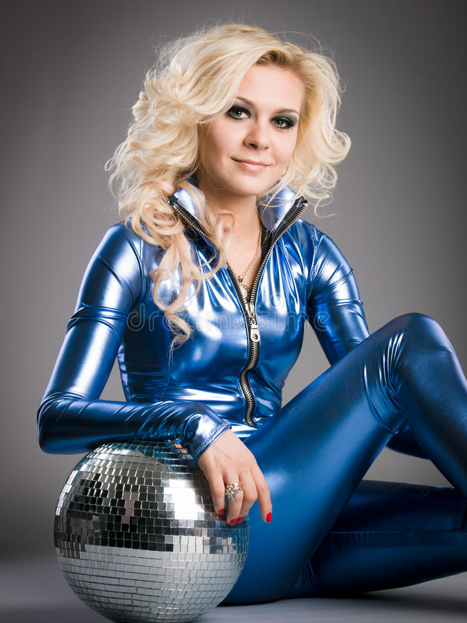 Disco girl with mirror ball. Smiling disco girl is posing with the mirror ball royalty free stock photos