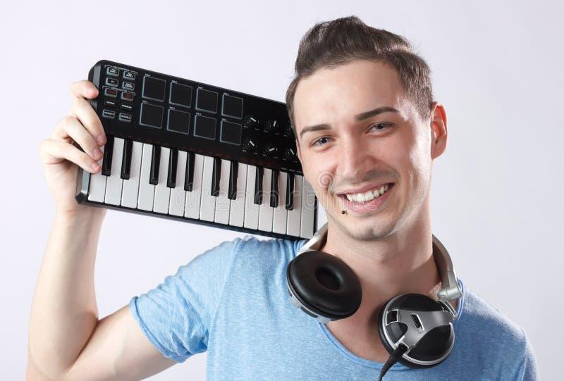 Disco-jóquei com auscultadores e teclado de midi fotografia de stock