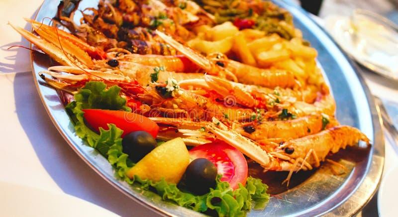 Disco mediterráneo de los mariscos con los langoustines y la ensalada fotografía de archivo