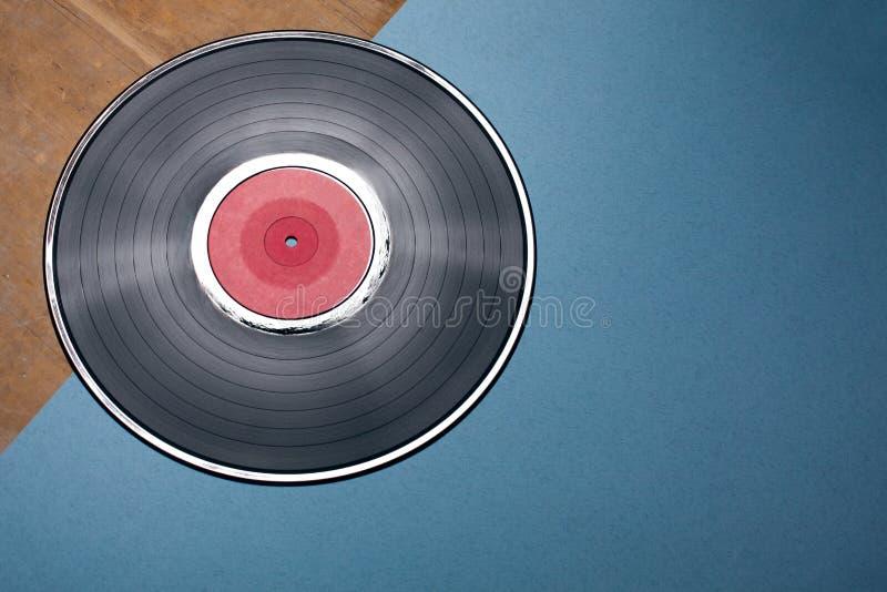 Disco musicale del vinile su fondo blu e di legno; immagine stock libera da diritti