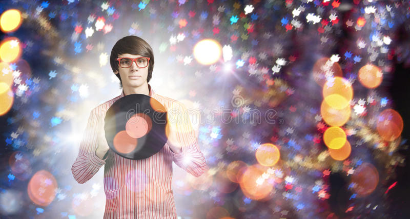 Disco party. Young handsome man with disco plate in hands royalty free stock photo