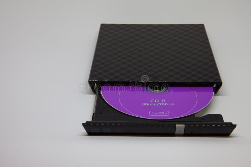 Disco porpora del CD nell'azionamento nero immagini stock