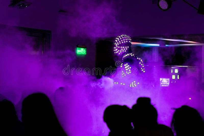 Disco a robot in a light suit with smoke stock photography