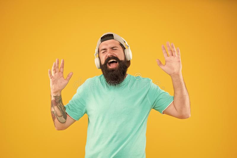 Disco sound. Bearded man relaxing with melodious sound on yellow background. Hipster wearing earphones playing. Electronic sound. Brutal guy listening to sound royalty free stock photography