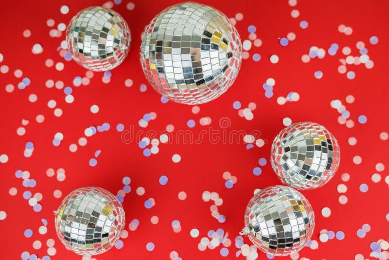 Disco-Spiegel-Kugel Weihnachtsbaum Spielzeug auf einem hellen festlich roten Hintergrund mit zerstreuten Konfetti Weihnachten und lizenzfreie stockbilder