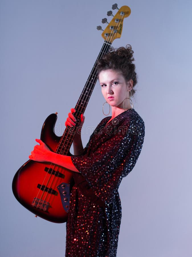 Disco-style photo of a girl with the guitar stock image