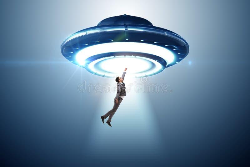 Disco volante che rapisce giovane uomo d'affari fotografia stock