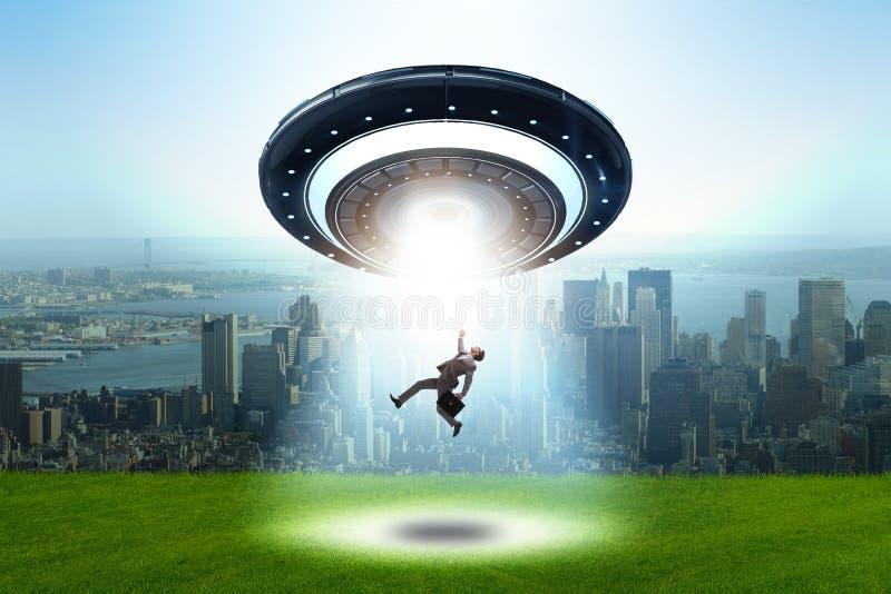Disco volante che rapisce giovane uomo d'affari immagine stock