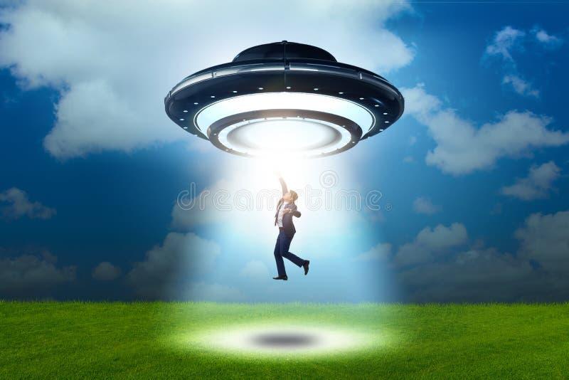 Disco volante che rapisce giovane uomo d'affari fotografie stock
