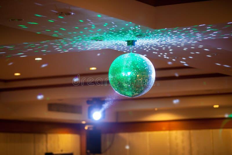 Discobal met heldere stralen, van de achtergrond nachtpartij foto De partij steekt discobal aan stock afbeelding