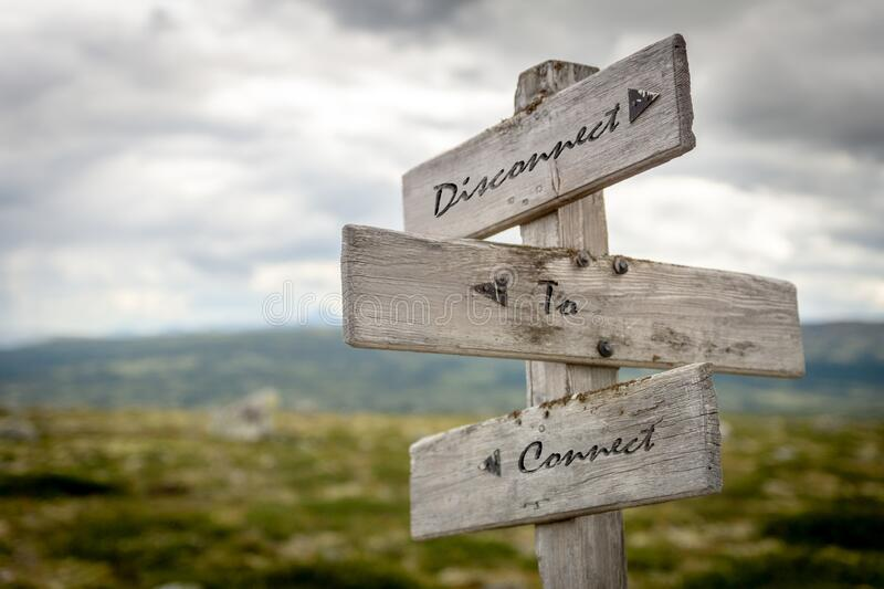 Disconnect to connect text on wooden signpost outdoors in nature. To simulate the use of internet, social media and the loss of our self in the modern day royalty free stock photos