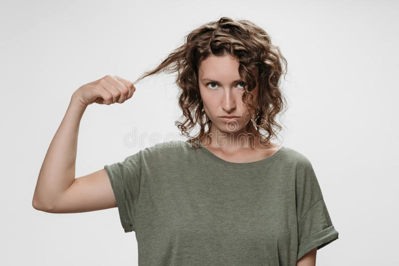 Frustrated discontent young curly brunette woman, frowns face with displeasure. Discontent curly brunette woman, frowns face with displeasure, holding a lock of stock photos