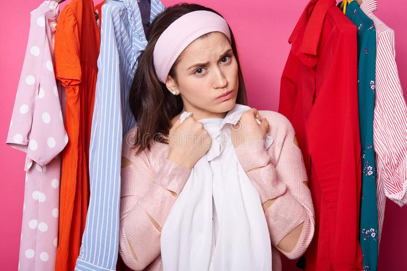 Discontent young female embraces white blouse. Beautiful woman wears rose sweater and hair band. Upset girl with lots clothes in royalty free stock photo