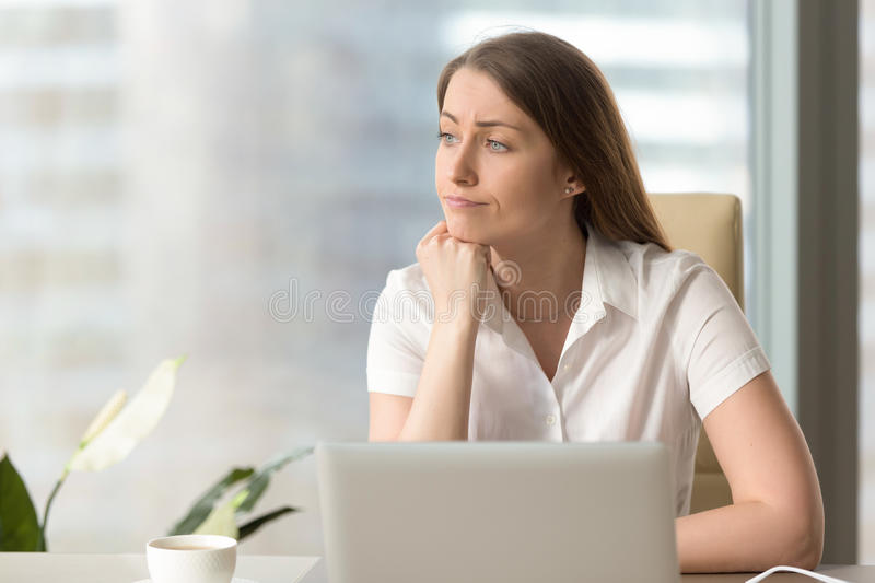 Discontented thoughtful woman holding hand under chin bored at w. Discontented thoughtful woman with hand under chin bored at work, looking away sitting near royalty free stock photos