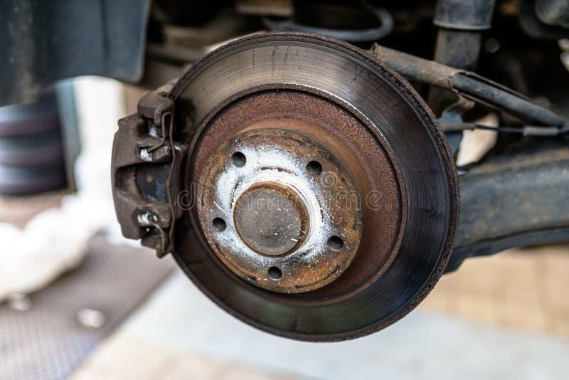 Discos del freno trasero con el calibrador y las zapatas de freno en el coche, en una elevación del coche en un taller fotografía de archivo