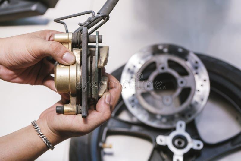 Discos do freio da verificação do mecânico da motocicleta, sistema de freio dianteiro das pastilhas dos freios na garagem, manute imagens de stock royalty free
