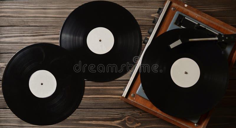 Discos do gramofone e do vinil em um assoalho de madeira Media retros foto de stock royalty free