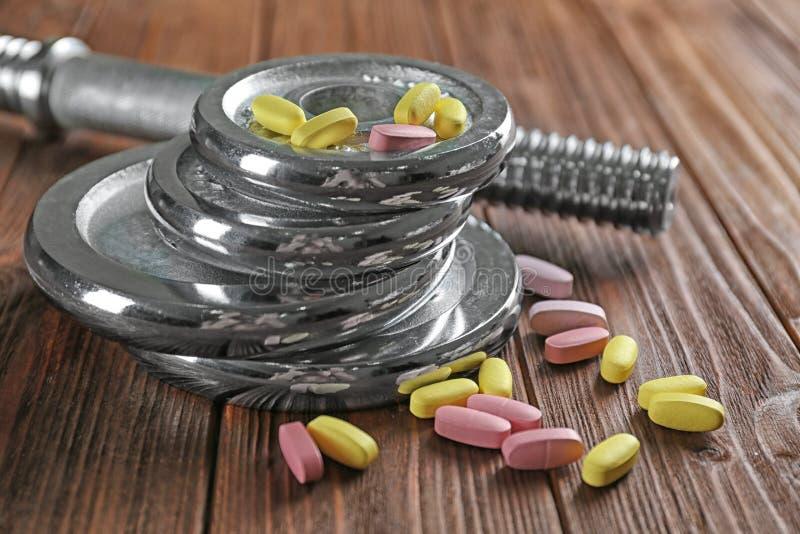 Discos e drogas do peso no fundo de madeira foto de stock royalty free