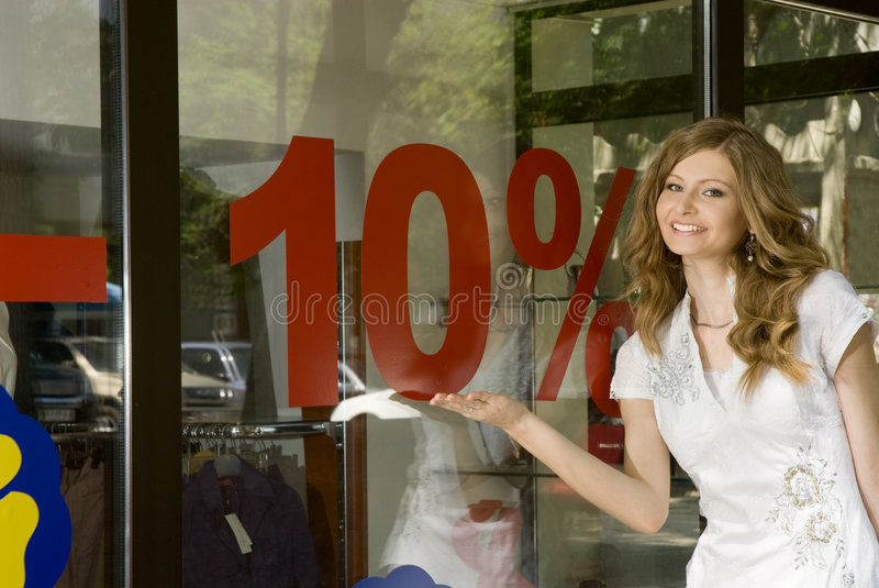 Discount 10%. Pretty woman shows 10% discount sign on a shop window royalty free stock image