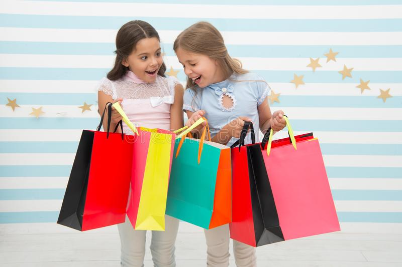 Discount concept. Kids cute girls hold shopping bags. Shopping discount season. Spending great time together. Children royalty free stock images