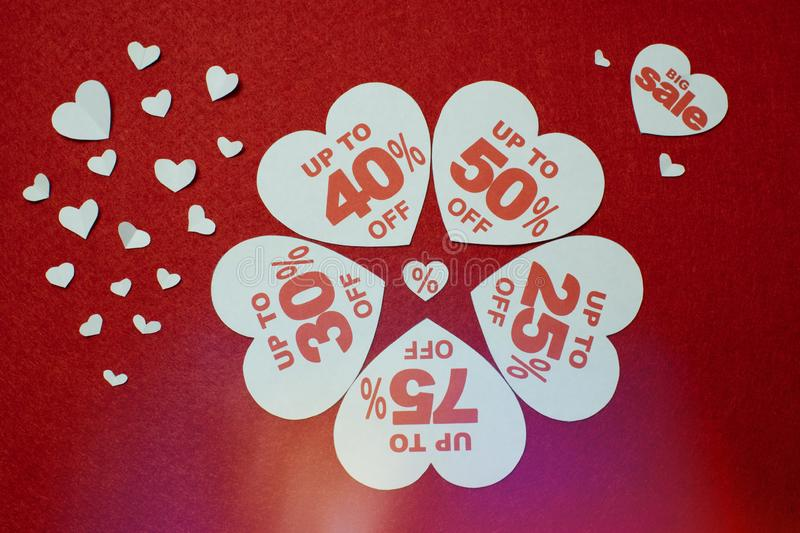 Discount promotion sale. Five big white hearts with per cent numbers surrounded by other small hearts stock photos