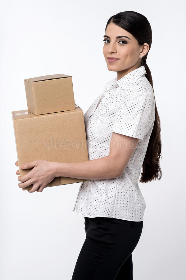 Discounted shopping now in online. Sideways of pretty woman carrying carton boxes royalty free stock photos