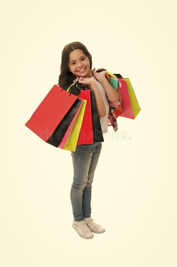 Discounts and promo codes. Girl carries shopping bags isolated on white background. Girl fond of shopping. Child cute. Shopaholic with bunch shopping bags black royalty free stock photography