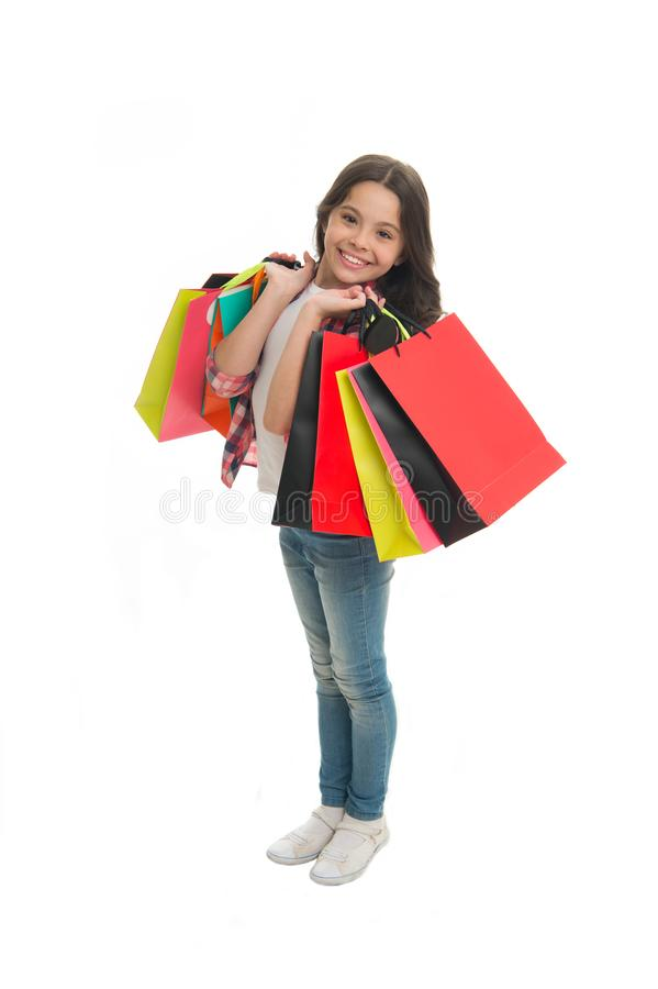 Discounts and promo codes. Girl carries shopping bags isolated on white background. Girl fond of shopping. Child cute. Shopaholic with bunch shopping bags black stock photo