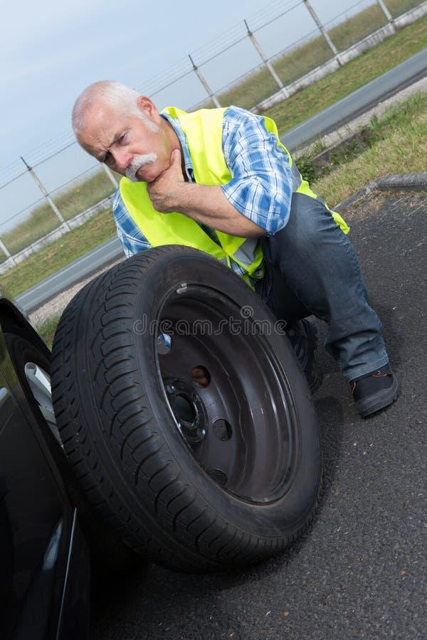 Discouraged退休了无法的人改变汽车轮胎 免版税库存图片