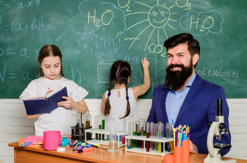Discover and explore properties of substances together. School club education. Teacher and pupils test tubes in royalty free stock photos
