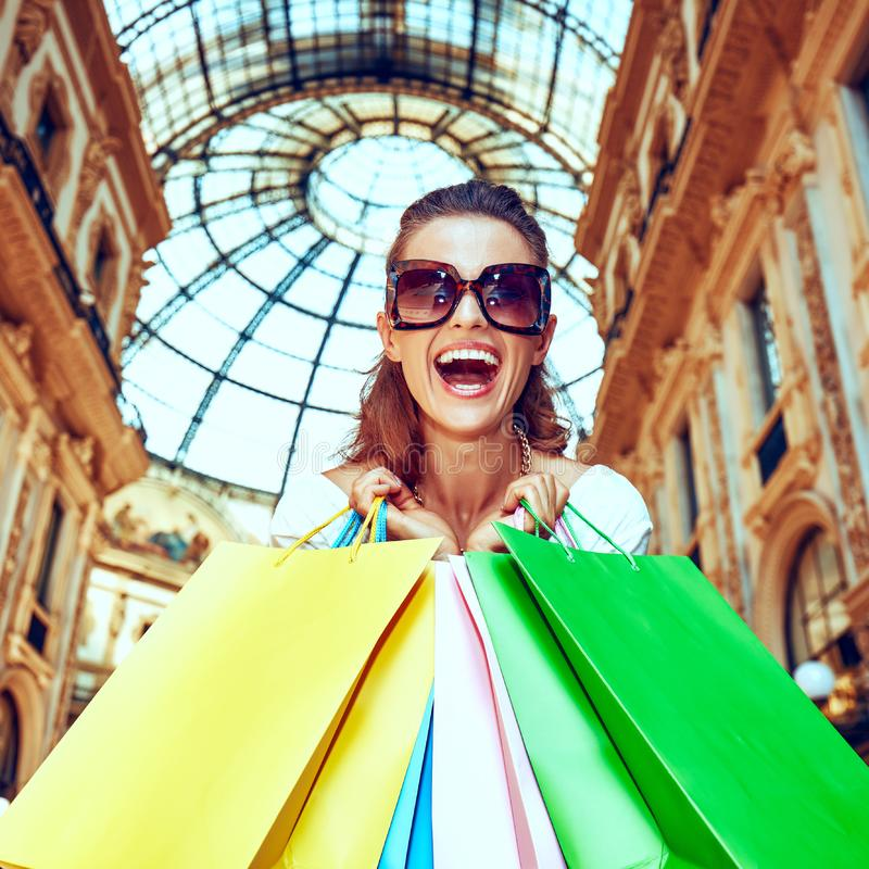Fashion monger with shopping bags in Galleria Vittorio Emanuele. Discover most unexpected trends in Milan. Portrait of smiling fashion monger in eyeglasses with stock image