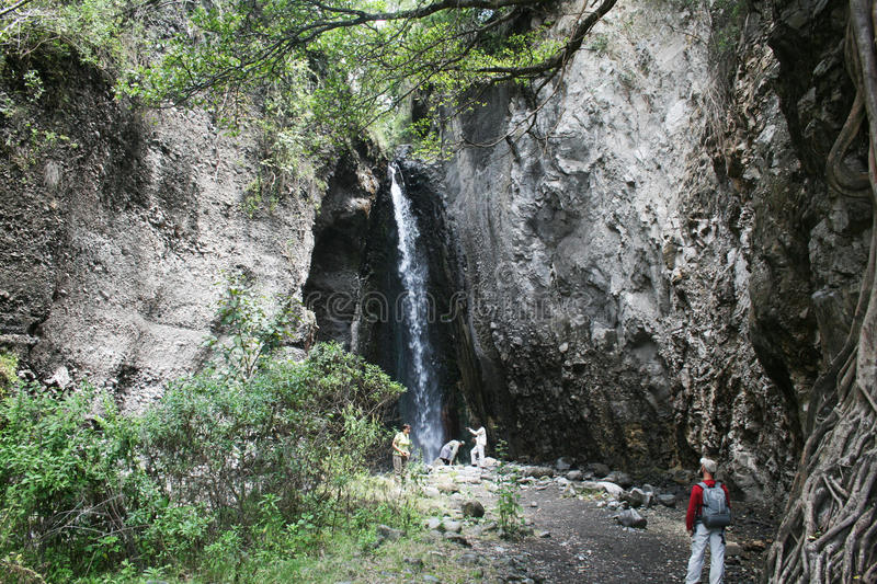 Discovery africa. Tourists near a waterfall during a walking safari in the arusha park in tanzania stock image