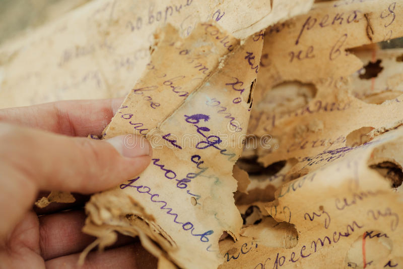 Discovery of old documents, letters of past centuries or paper manuscripts in unknown language, spoiled by time. royalty free stock photos