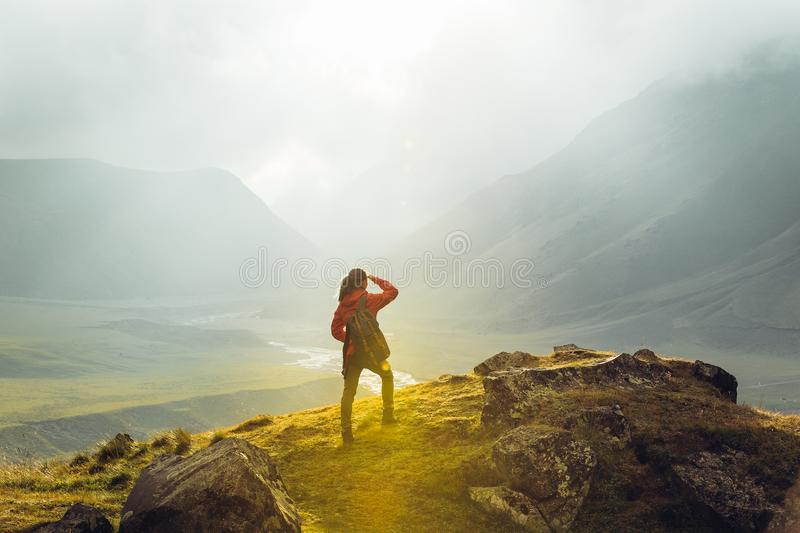 Discovery Travel Destination Concept. Hiker Young Woman With Backpack Rises To The Mountain Top Against Backdrop Of Sunset, Rear V stock photos