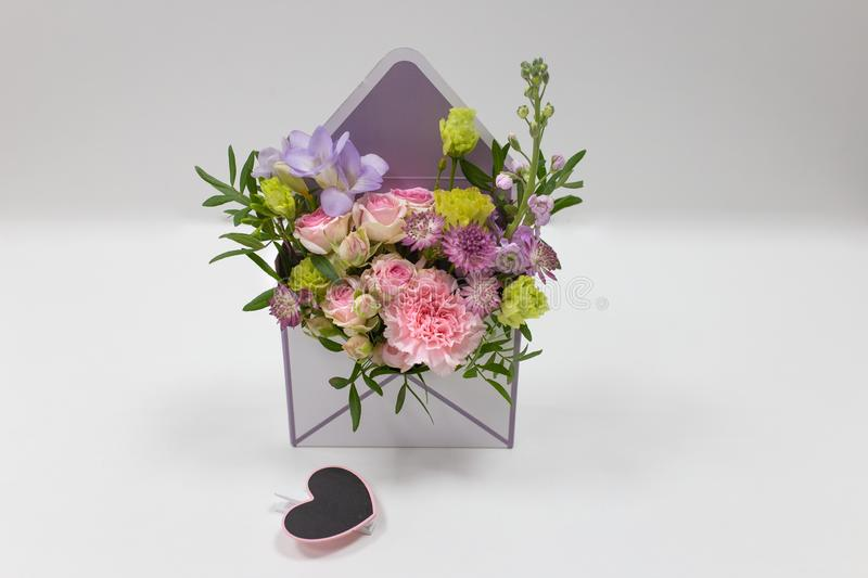 Discreet floral arrangement of fresh flowers in a box in the form of an envelope on a light background. Flowers: carnation, rose,, leaves. Colors: pink, green stock images