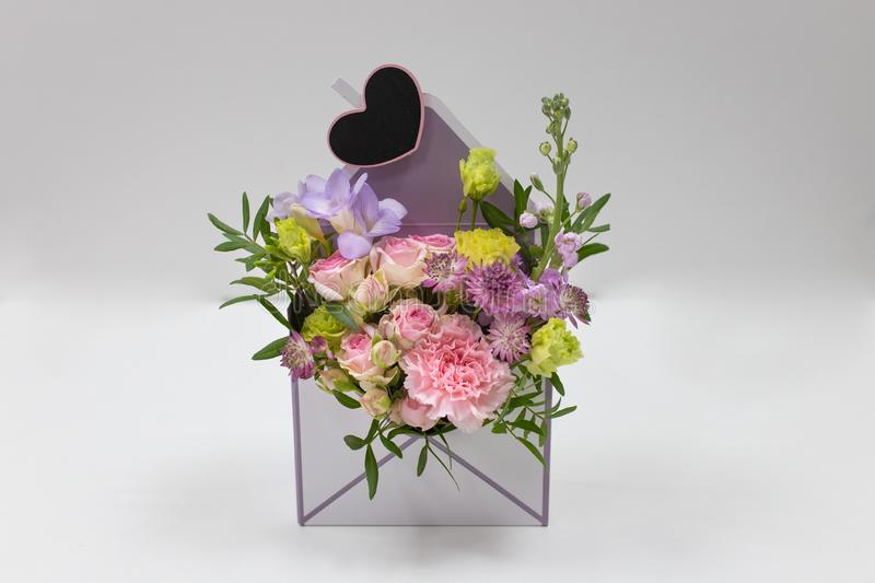 Discreet floral arrangement of fresh flowers in a box in the form of an envelope on a light background. Flowers: carnation, rose,, leaves. Colors: pink, green royalty free stock photos