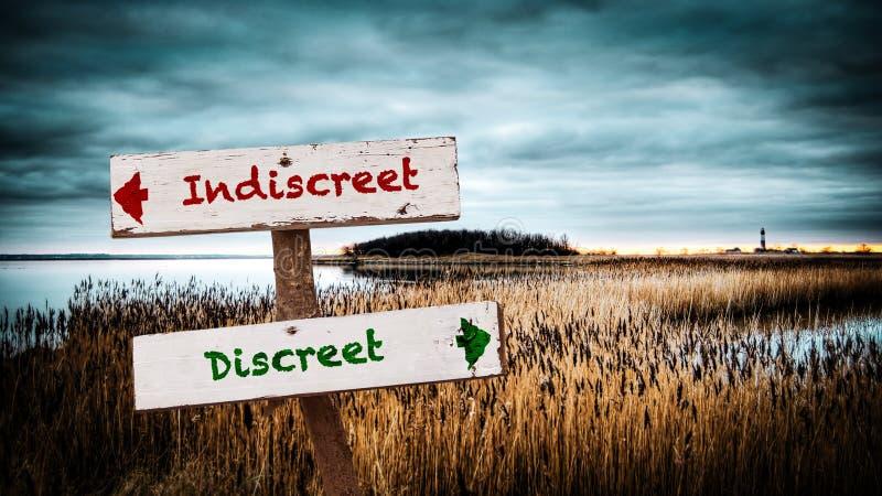 Discreet tegenover Indiscreet straatteken stock afbeeldingen