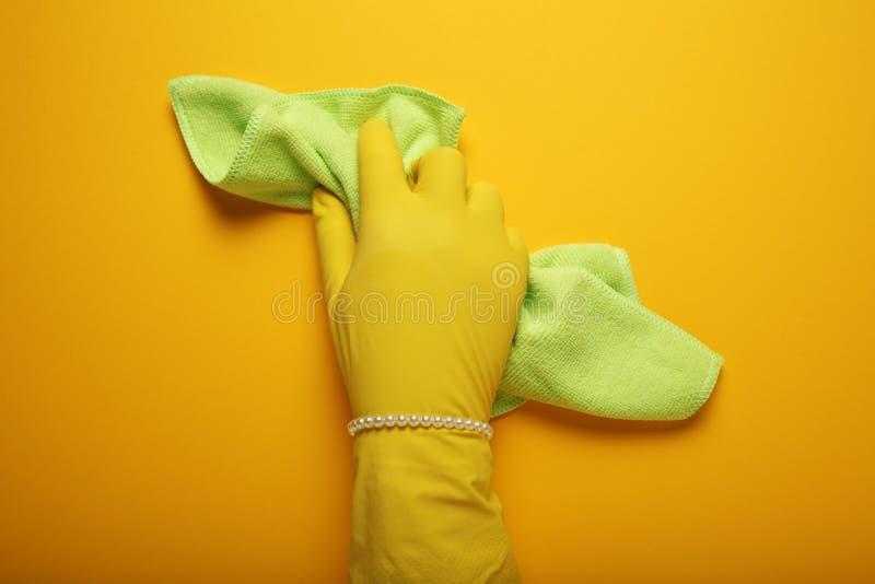 A discriminação e a humilhação das mulheres, mão com o bracelete da pérola na luva limpam Trabalhos domésticos da mulher, igualda foto de stock