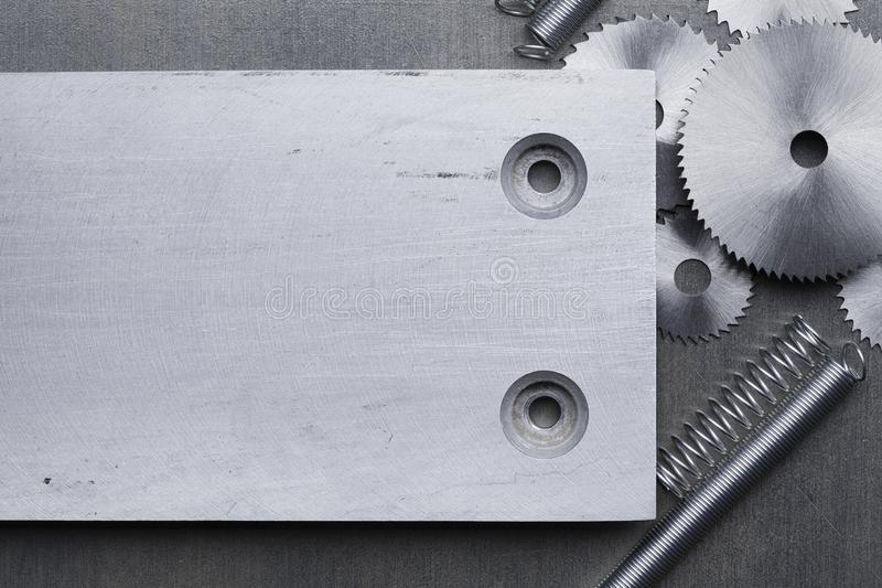 Discs for circular saw, metal springs and aluminum plate on a metal table. Discs for circular saw, metal springs and aluminum plate on a gray metal table royalty free stock photo