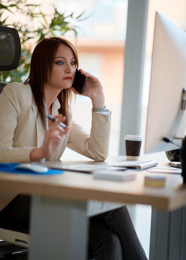 Discurso al cliente en el teléfono - mujer que trabaja en un perno prisionero del diseño foto de archivo libre de regalías