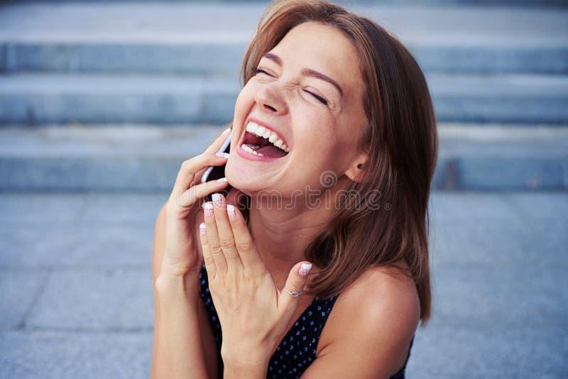 Discurso fêmea alegre atrativo no telefone e no si de riso imagens de stock