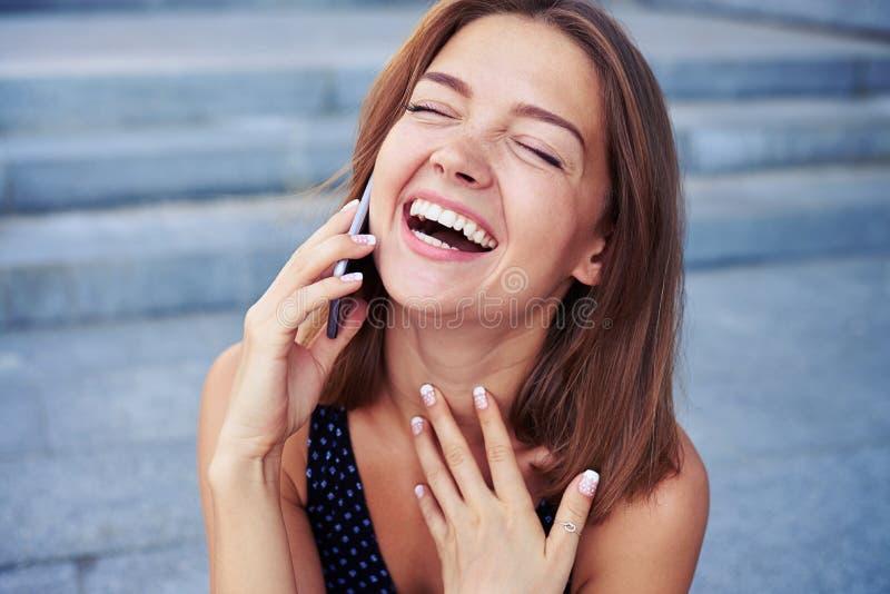 Discurso fêmea atrativo no telefone e riso sinceramente imagens de stock royalty free