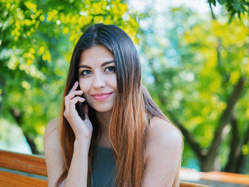 Discurso fêmea em seu telefone celular Tecnologia, conceito do smartphone A mulher tem a conversação com amigo Fala e foto de stock