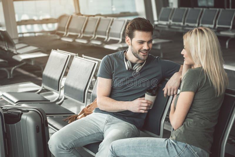 Discurso masculino alegre com a mulher positiva no aeroporto fotografia de stock royalty free