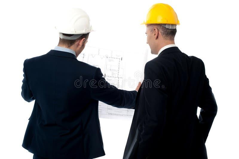 Discusión de los ingenieros de sexo masculino de la parte posterior imagen de archivo libre de regalías