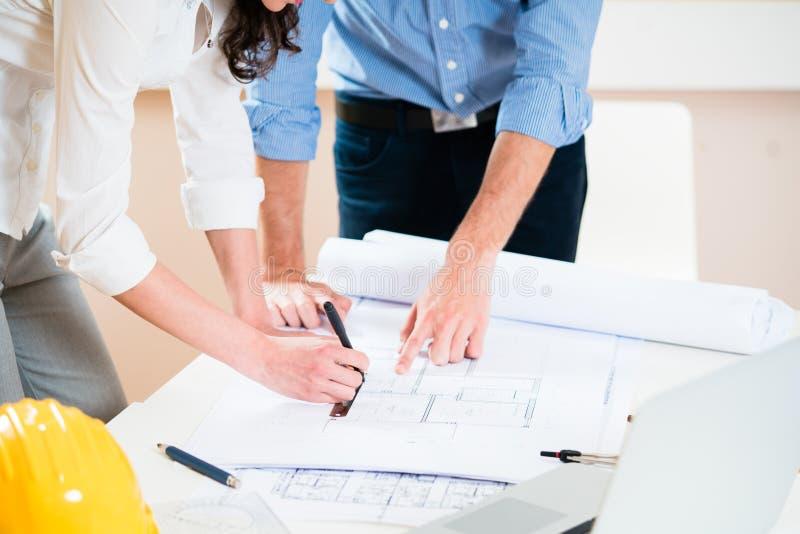 Discusión de los planes de la construcción en oficina de arquitectos imagenes de archivo