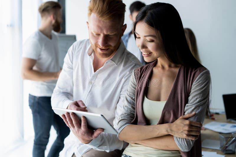 Discusión de nuevo proyecto del negocio Dos personas jovenes felices que sonríen y que miran la tableta digital mientras que trab fotografía de archivo